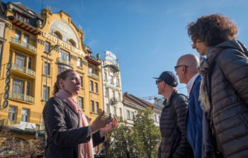 tour guide talking to group about large yellow building in background