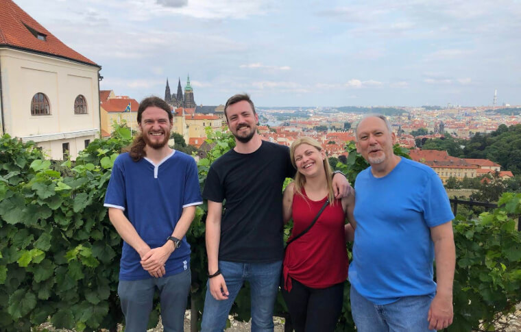 group of people smiling before skyline of prague city