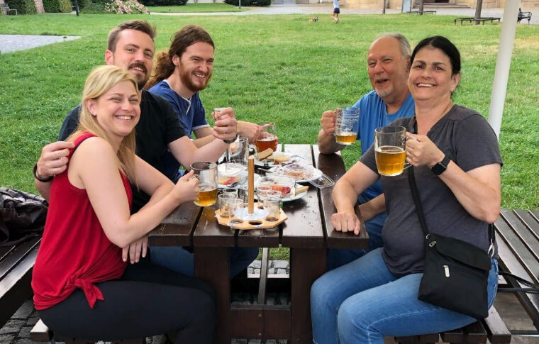 group of people raising beers at park bench
