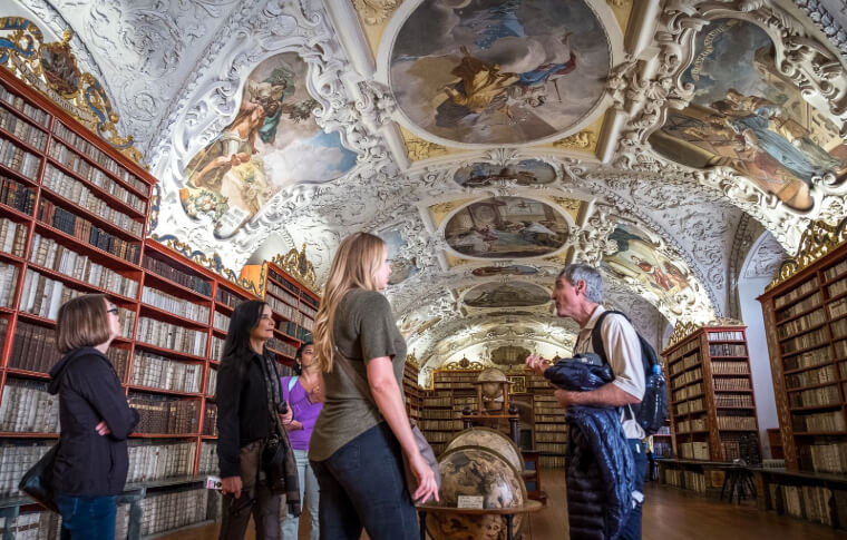 group of people in old library looking up at painted ceiling