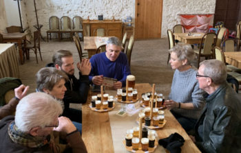 group of people sitting at table with paddles of beers