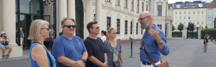 A guide speaks to visitors outside the palace.