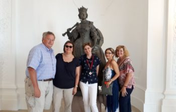 Visitors pose in front of sculpture.