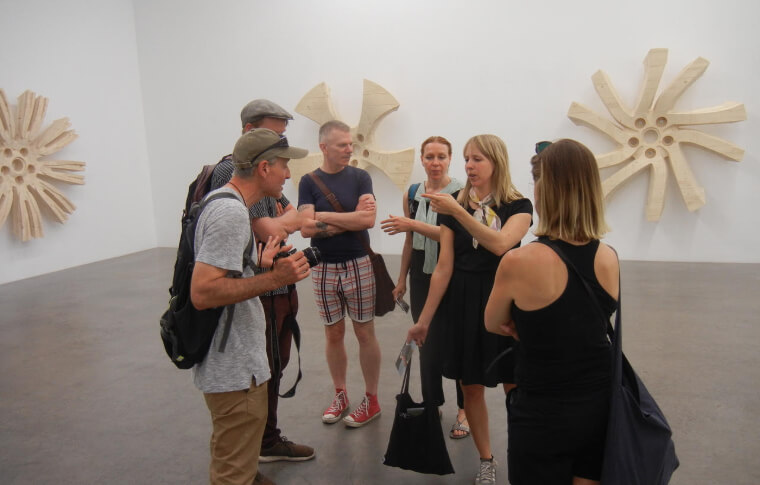 The group gather around a guide inside a gallery.