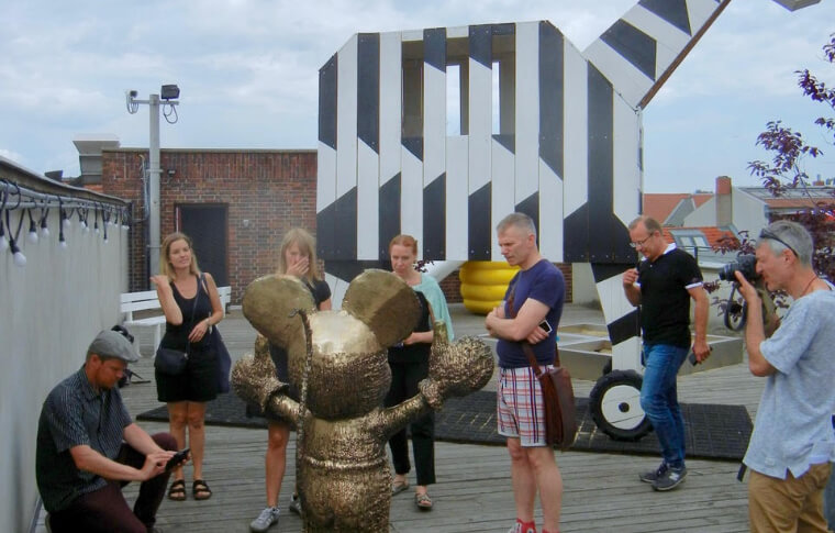A group of visitors surround a gold statue of a mouse.