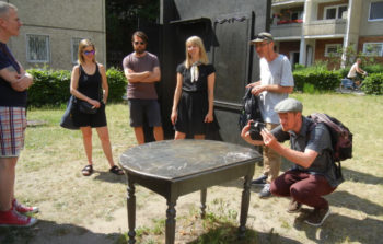 The group surround a table in an outside gallery.
