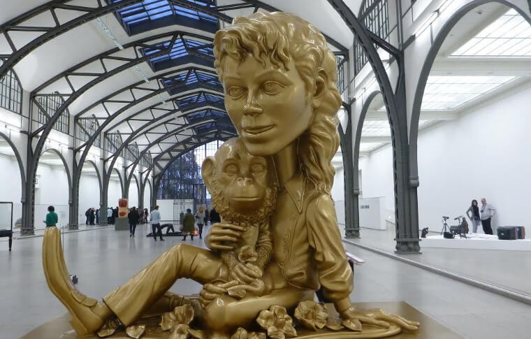 statue with large head holding child