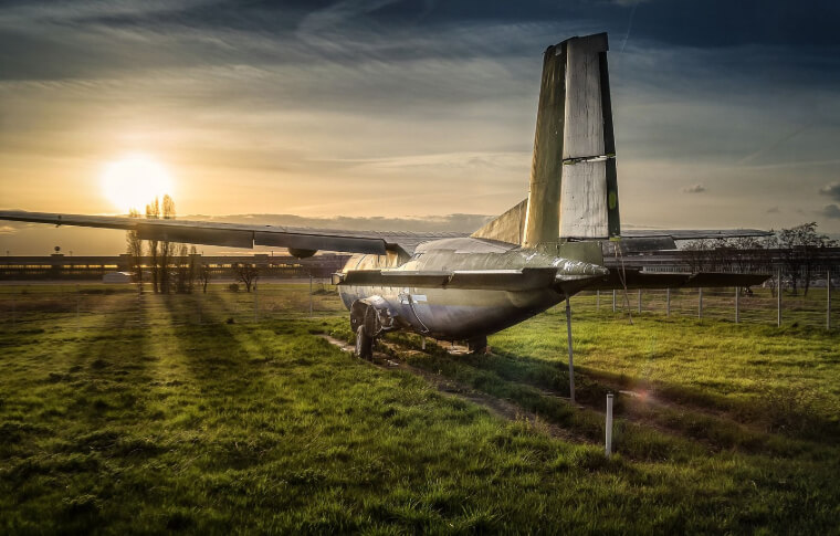 small plane on grass at sunset