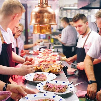 group of people in aprons standing around a bench full of food