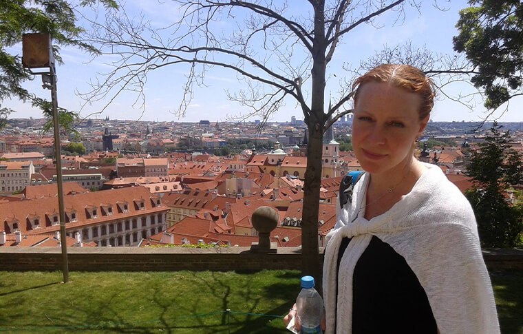 woman smiling in front of view over red roofed city