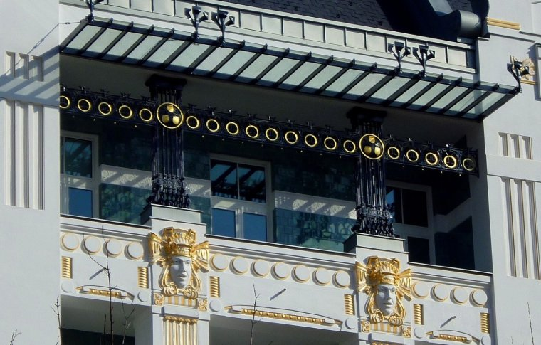 Faces ornately carved into the outside of a building, decorated with gold.