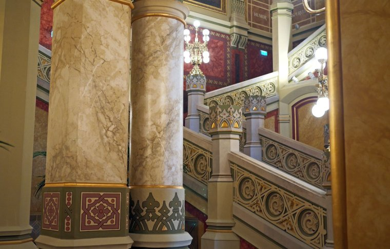 Gold and art nouveau patterns on a staircase going upstairs.