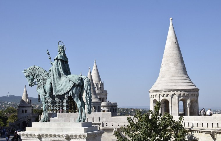military statue of man on horse with white palace tower in background