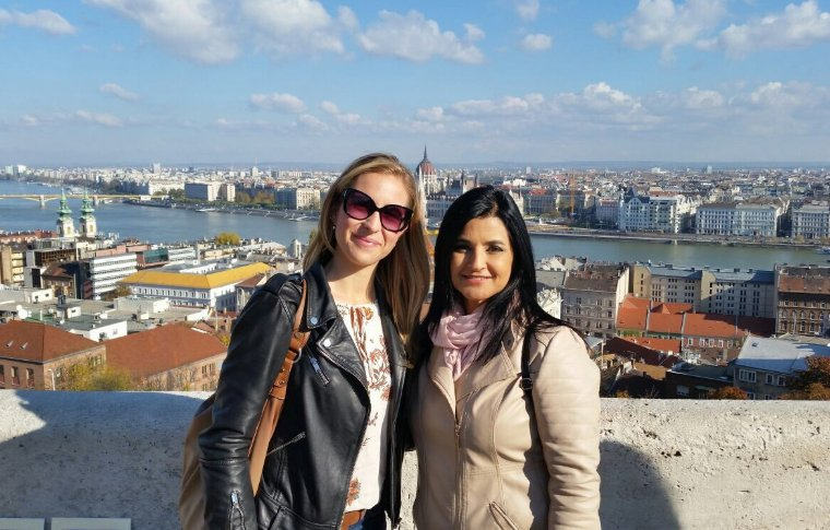 two women smiling overlooking city skyline and river