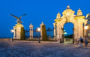 ornate gate with statues litup at night