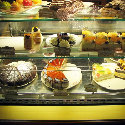 A glass cabinet filled with different cakes.