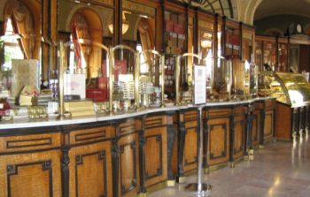 Old fashioned wooden cabinets and mirrored walls of a Budapest cafe.