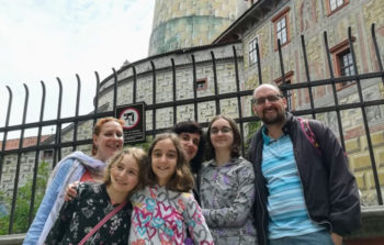 family smiling in front of medieval castle