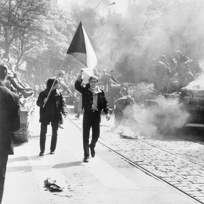 black and white photo of men walking next to car on fire