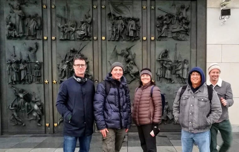 group of people smiling in front of large metal door with embossed figures