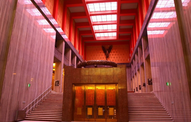 red lit stone interior with grand staircase and red skylight