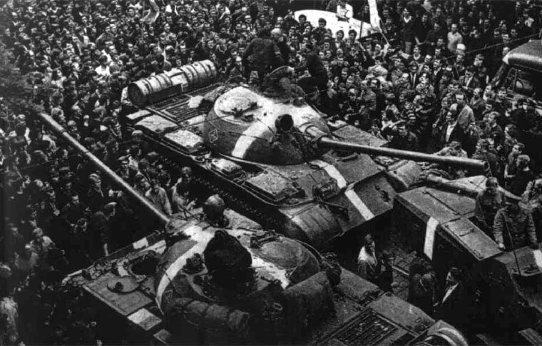 black and white image of tank moving through crowd of people