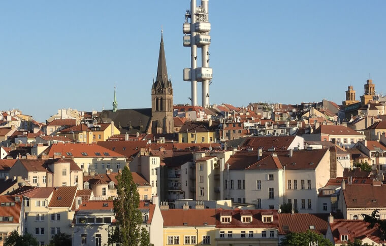 view of prague skyline with futuristic tower amongst older red tiled buildings