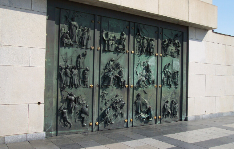 large metal wall with figures embossed