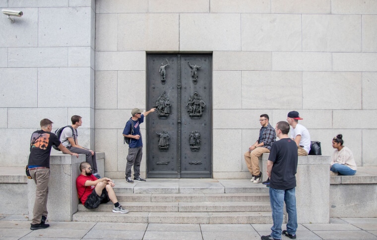tour guide pointing to large metal door on the top of stone steps