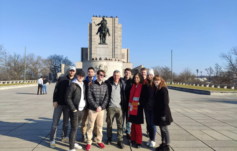 group of people smiling in front of large statue of man on horse