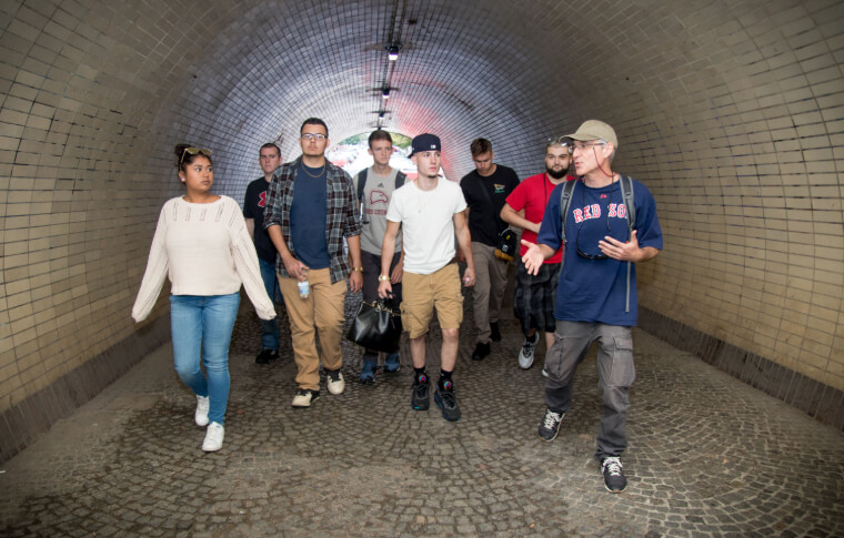 tour guide explaining something to guests while walking through tunnel