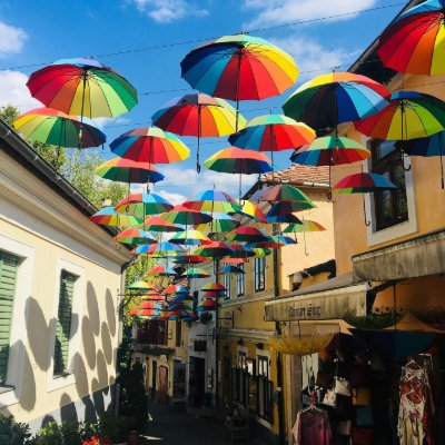 Rainbow-colored umbrellas over a narrow street in Budapest