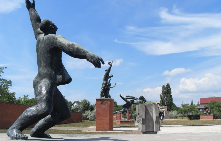 statue of man with his arm in the air in movement