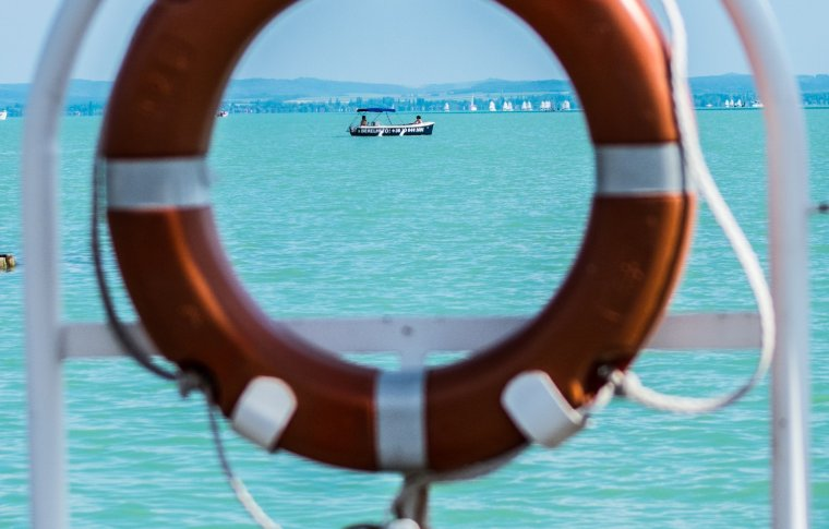 boat on clear blue water as seen through floating boat hoop