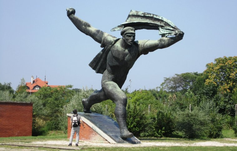 statue of man running holding flying material