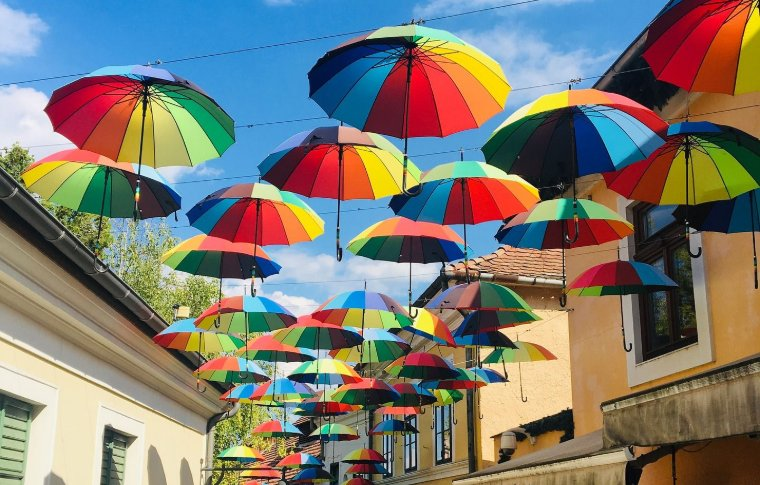 rows of rainbow umbrellas hanging in the air