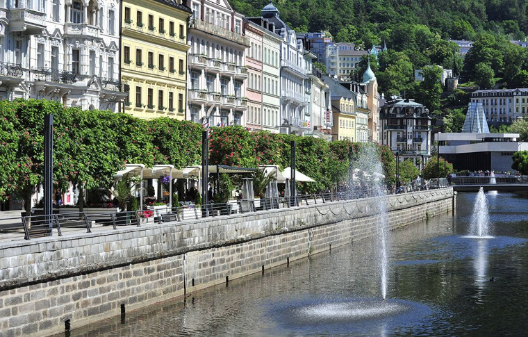 row of colourful buildings in front of water with fountain
