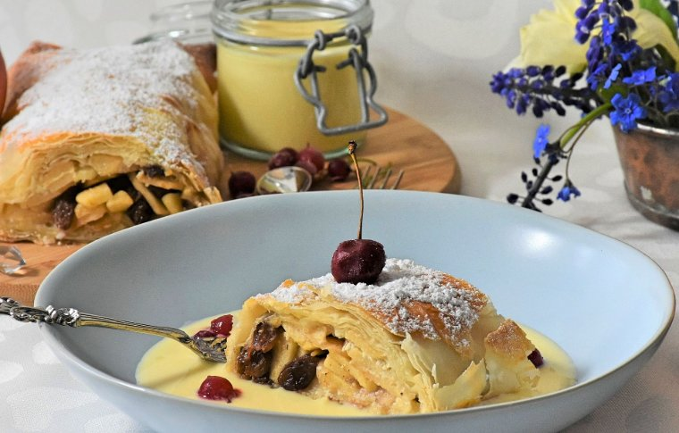 custard and pastry with cherry and icing sugar on top