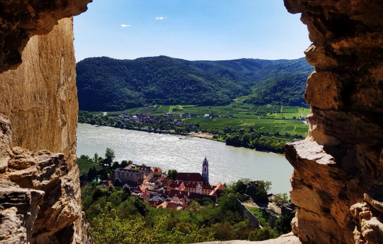 view of river and mountains through stone archway