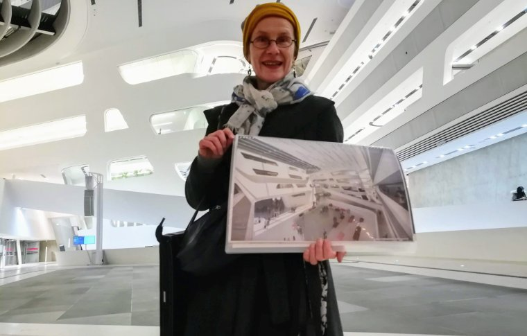 woman holding large image of museum interior