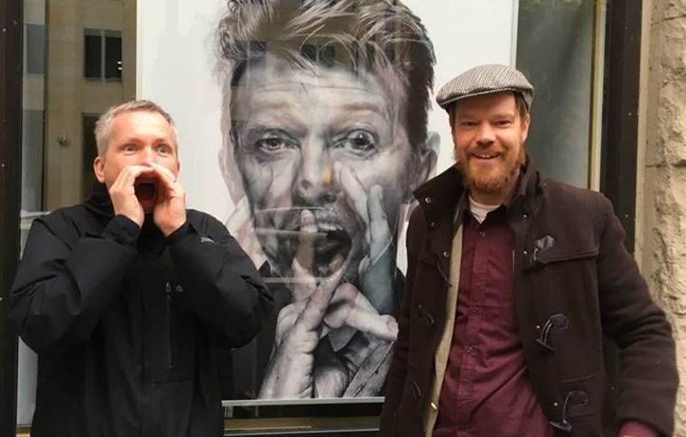 Two tourists stand either side of a picture of David Bowie.