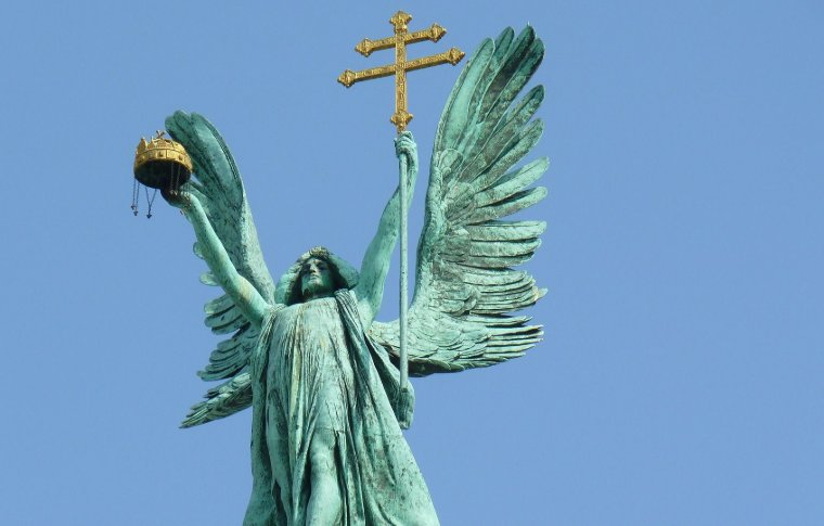 large statue of angel holding golden cross of lorraine