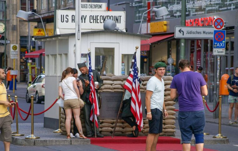 A group of tourists standing next to American flags in Berlin