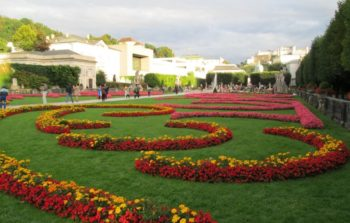 large curated garden with red and yellow flowers in semi circle layout