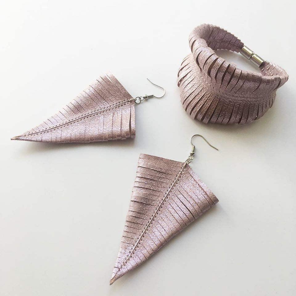 a pair of earrings and ring in light pastel pink