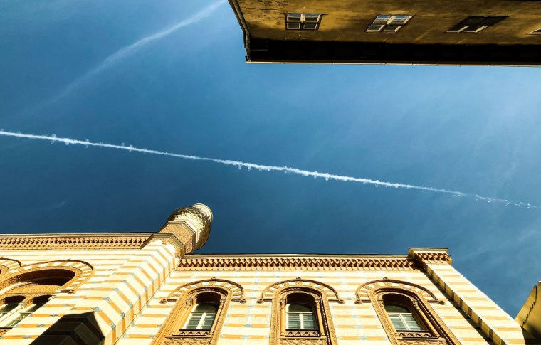 The chandeliers inside the Kazinczy Street Synagogue, Budapest and a plane trail in the sky.