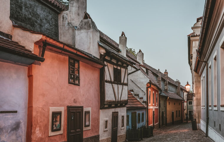 old and small buildings along street in pinks and white