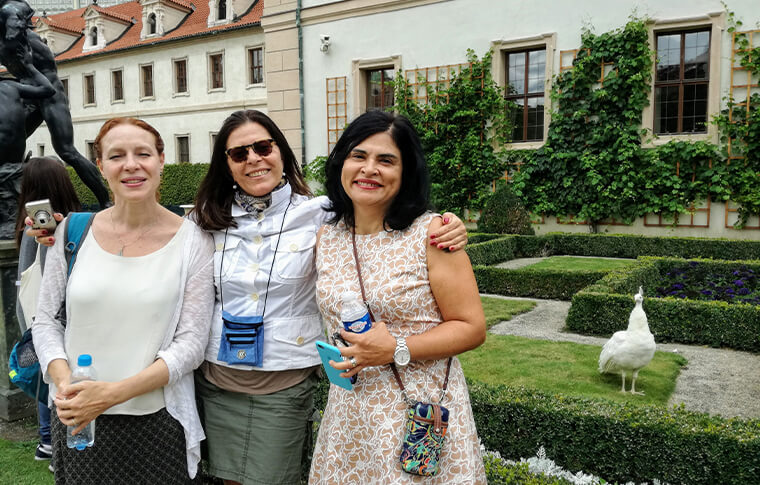 3 women smiling in front of curated garden courtyard