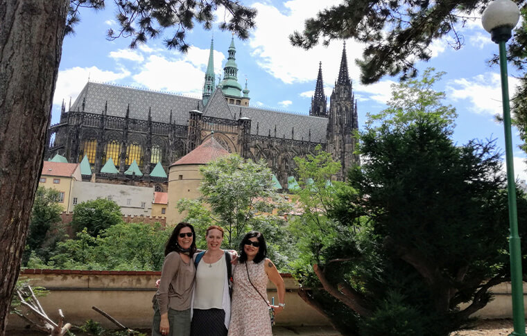 3 women smiling in front of garden with large church in background