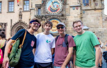 four men in tshirts smiling in front of clock